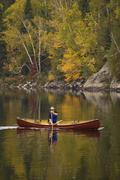 Elderly man canoeing on Oxtongue Lake in autumn, Mukoka, Ontario, Canada. Stock Photos