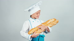 Baker girl 7-8 years child holds bread baguettes and smiling at camera isolated Stock Footage
