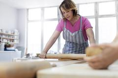 Woman rolling clay with rolling pin in studio Stock Photos