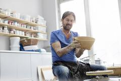 Portrait confident mature man holding bowl at pottery wheel in studio Stock Photos