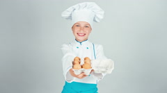 Chef cook girl 7-8 years holding tray of egg and gives you it at camera Stock Footage