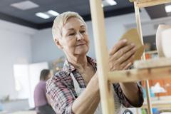 Smiling senior woman placing pottery on shelf in studio Stock Photos