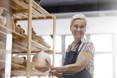 Smiling senior woman placing pottery vase on shelf in studio Stock Photos