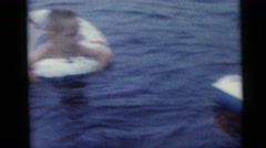 1967: two children swim with an inflatable ring while two women supervise Stock Footage