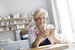 Portrait smiling mature woman holding bowl in pottery studio Stock Photos