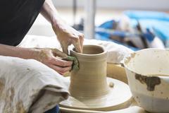 Woman using pottery wheel in studio Stock Photos