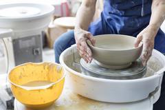 Senior man using pottery wheel in studio Stock Photos