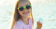 Close up portrait happy child girl eating ice cream sitting near fountain Stock Footage