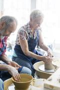 Senior couple using pottery wheels in studio Stock Photos