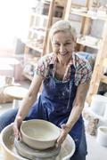 Portrait smiling senior woman using pottery wheel in studio Stock Photos
