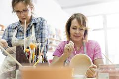 Mature women painting pottery in studio Stock Photos