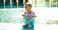 Portrait child girl 7-8 years in sunglasses sitting relaxing near fountain Stock Footage