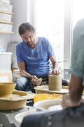 Mature man using pottery wheel in studio Stock Photos