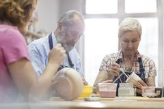 Senior couple painting pottery in studio Stock Photos