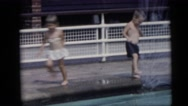 1967: young children in swimsuits frolic, run and play in and around pool Stock Footage