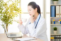 Doctor drink coffee and using computer, healthcare and medicine concept Stock Photos