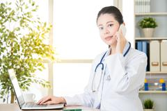 Doctor explain patient's condition by smart phone and computer Stock Photos