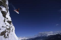 A snowboarder jumping off a cliff, Marmot Basin, Alberta, Canada. Stock Photos