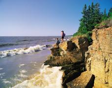 Couple on sedimentary rock cliff, Hecla Provincial Park, Manitoba, Canada Stock Photos