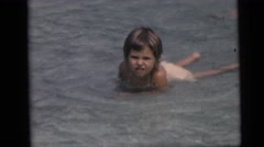1967: children swimming and playing and splashing in shallow water on the beach Stock Footage