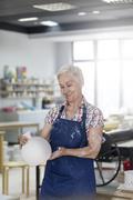 Smiling senior woman holding pottery vase in studio Stock Photos