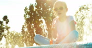 Portrait girl 7-8 years in sunglasses blowing soap bubbles sitting near fountain Stock Footage