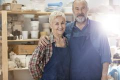 Portrait smiling senior couple wearing aprons in pottery studio Stock Photos
