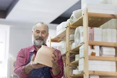 Senior man examining pottery bowl in studio Stock Photos