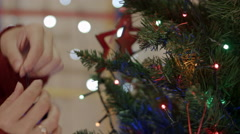 Close up of women hands hanging vintage toy on christmas tree Stock Footage