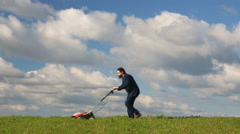 Businessman with a lawnmower Stock Footage