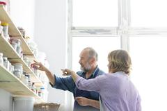 Man and woman browsing art supplies on shelves in art studio Stock Photos