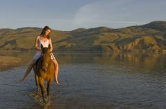 A young lady rides bareback on the shores of the Thompson River, just before Stock Photos