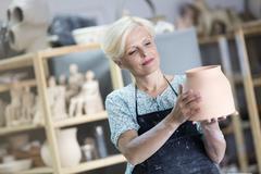 Mature woman holding pottery vase in studio Stock Photos