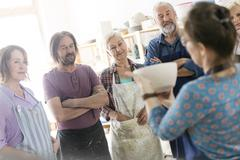 Teacher showing pottery bowl to mature students in studio Stock Photos