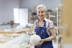Portrait smiling senior woman holding pottery vase in studio Stock Photos