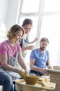 Teacher guiding mature couple using pottery wheel in studio Stock Photos