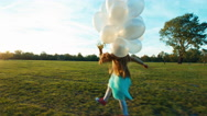 Child running across the field at sun in sunset and holds her white balloons Stock Footage