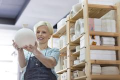 Smiling woman holding pottery vase in studio Stock Photos