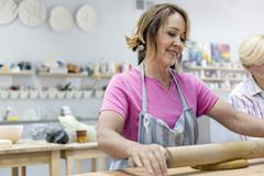Smiling mature woman rolling clay with rolling pin in pottery studio Stock Photos
