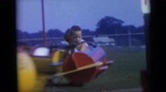 1967: little kids riding airplanes on an amusement park ride. CAMDEN, NEW JERSEY Stock Footage
