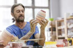 Mature man painting pottery vase in studio Stock Photos
