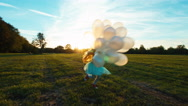 Happy child girl 8-9 years old running across field and spinning with balloons Stock Footage