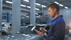 Smiling mechanic using a tablet pc at the repair garage service Stock Footage