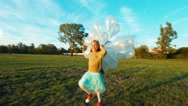 Child 8-9 years old running across field at sun in sunset with balloons Stock Footage