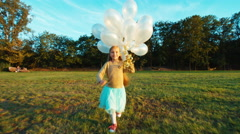 Child 8-9 years old running at camera and holds her white balloons and smiling Stock Footage