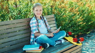 Happy girl using smartphone sitting on the bench in the park and smiling Stock Footage