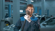 Portrait of Professional smiling car mechanic working in modern auto repair Stock Footage