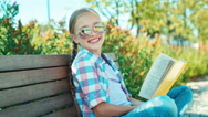 Portrait child 7-8 years reading book in sunglasses sitting on the bench Stock Footage