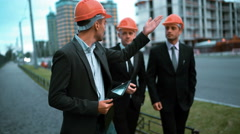 Construction worker and businessmen talking on site Stock Footage