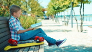 Portrait child 7-8 years reading book sitting on the bench and looking at camera Stock Footage